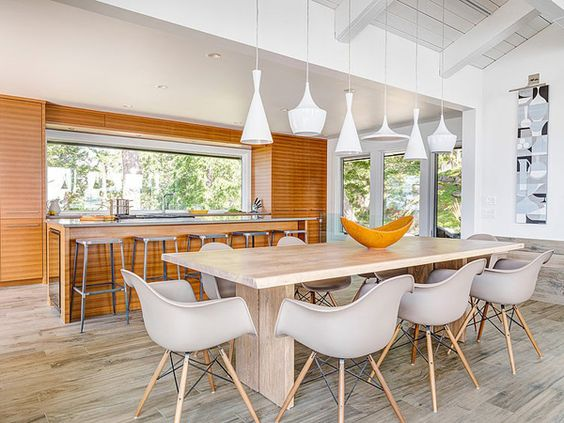 I love the contemporary modern pendant lighting that are hung at different lengths..a great focal point.. this kitchen is super clean and modern, but I do like how the designer incorporates homey details to keep the interior of this home looking comfortable and not stark...just like a beach house should be..
