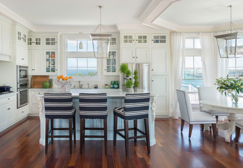 Bring a touch of color to a white kitchen with a touch of nautical style elements. This kitchen is gorgeous, I love the designer choice to let the view be the star of this room. The nautical blue and white kitchen stools, flowers and greenery is all the color this kitchen needs.