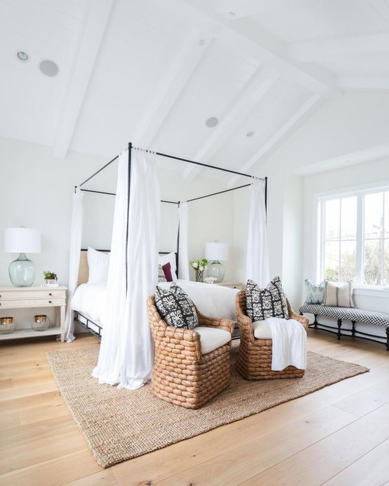 """Designer Wendy Blackband of Blackband Design says, """"The light-washed hardwood floors paired with the painted ceiling beams give this farmhouse a modern twist. We combined soft, breezy fabrics with natural textures and tones to give off a casual coastal vibe. When choosing fabrics we looked for materials that would read as simple, unassuming, and comfortable. The iron canopy bed complements the height of the ceiling, keeping everything proportionally balanced. When designing coastal homes we also look for organic materials like jute and seagrass. Using natural fiber rugs is a great way to add warmth and texture to a room, and they are the perfect rugs for layering.""""  via"""