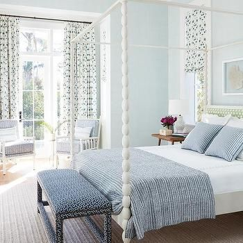 A delightful blue and white bedroom starring this white spindle canopy bedroom, at the foot of the bed is a blue bench. The bedding features a blue and white striped pillow coverlet and pillow shams, layered with white scallop pillows. The headboard is upholstered with a light green fabric. The accent chairs match the design of the white spindle design of the bed and that have blue cushions. The gorgeous floor length curtains add the final touch of elegance to this beautiful bedroom.