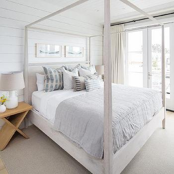 A tranquil bedroom has me wanting to move right in. Grey wash wood canopy bed dressed in white and gray bedding with plenty of plush pillows. A soft grey rugs anchors the room along with the blond wood nightstands. Side-by-side art pieces hang from a white shiplap wall above the bed.  Via