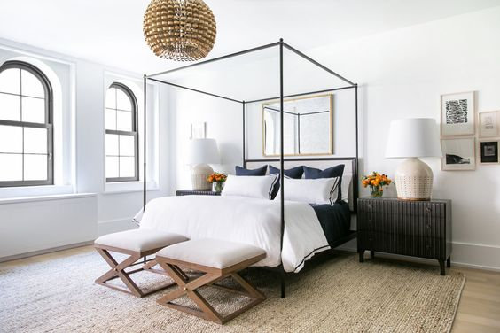 I love the balanced clean lines in this bedroom, stylish black and white bedroom, the black canopy bed is dressed with a plush white comforter and pillows, on either side black nightstands. One of my personal favorite.  via