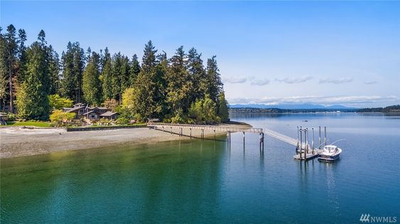 - This magnificent, custom designed home sits on the shores of Manzanita Bay with hundreds of feet of no-bank waterfront and a deep water dock. Bainbridge Island Real Estate.