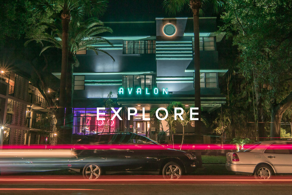 Nightime image of the front of the Avalon Hotel with cars zooming by.