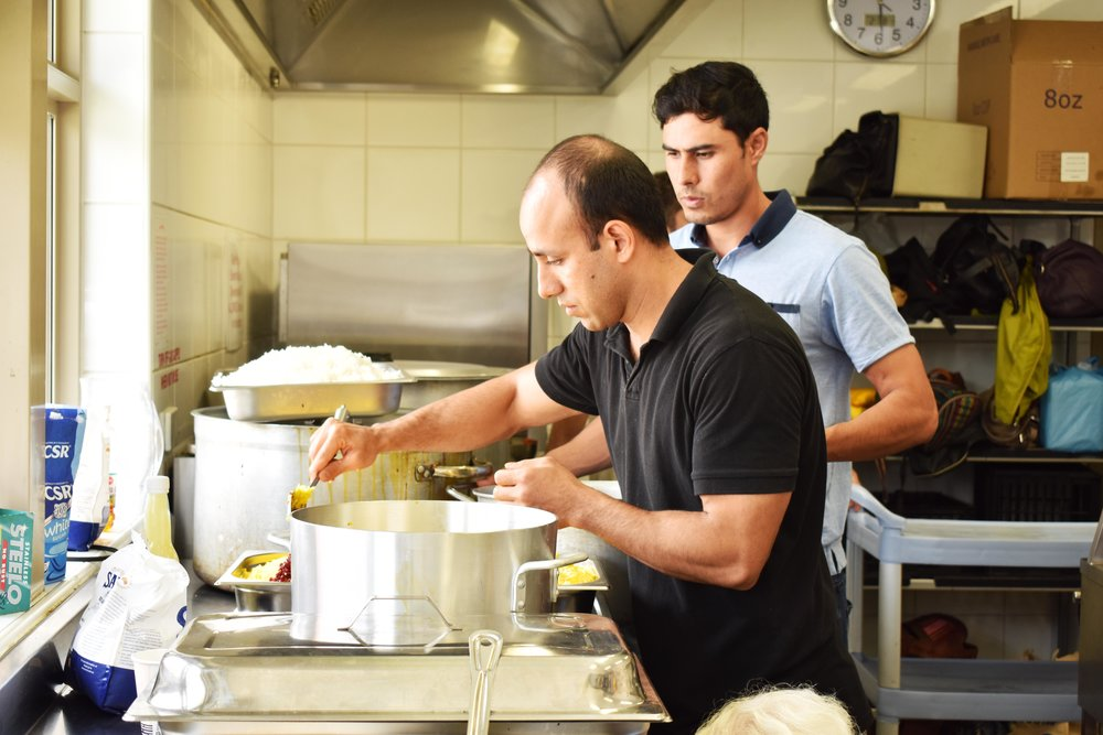 Mostafa cooking at SSI Community Kitchen with the help of another volunteer.