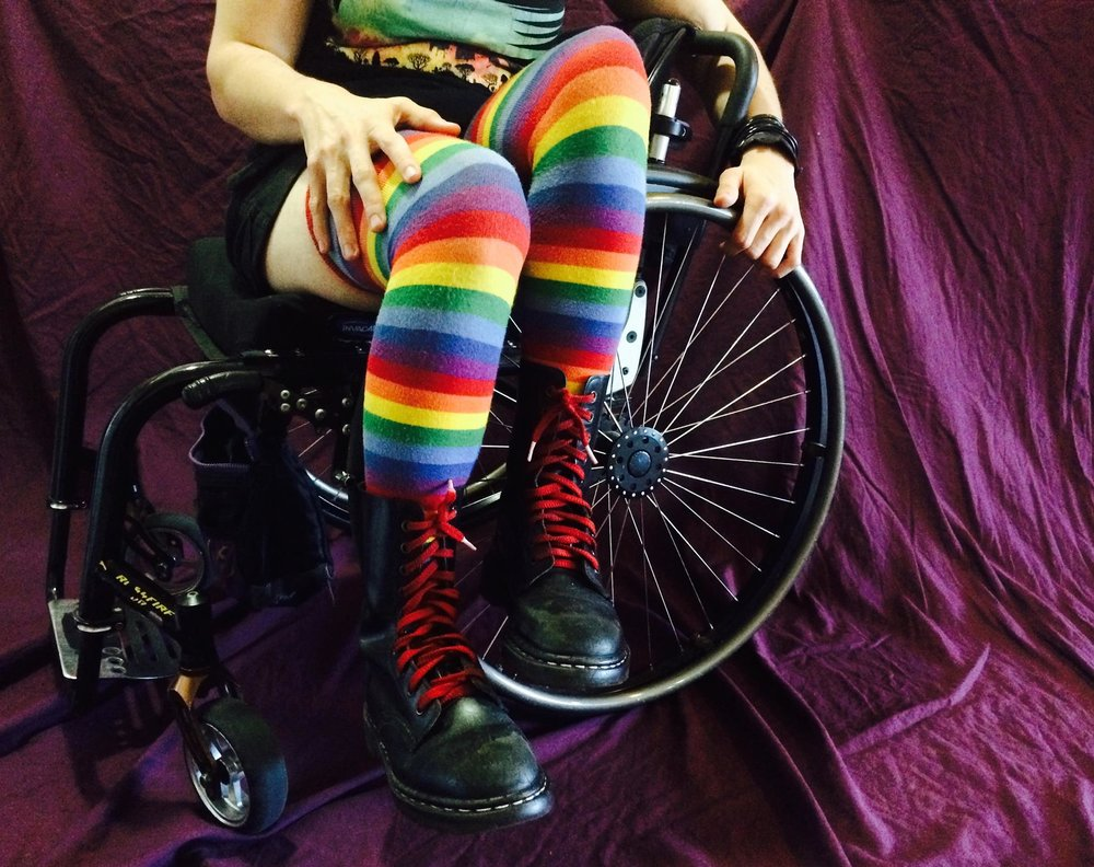 A white person wearing long rainbow socks on a purple background, sitting in a black wheelchair with their legs over the side of one of the wheels.