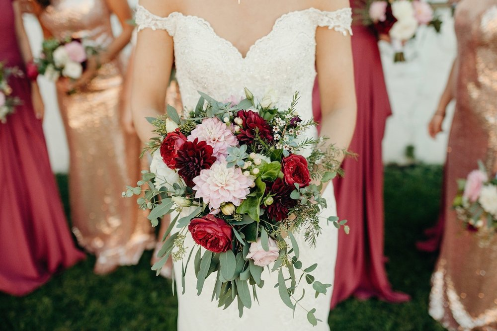 The bouquet: Dahlias, Wax Flower, Hypericum, Succulents, and Roses for color, Eucalyptus and Ivy for greens