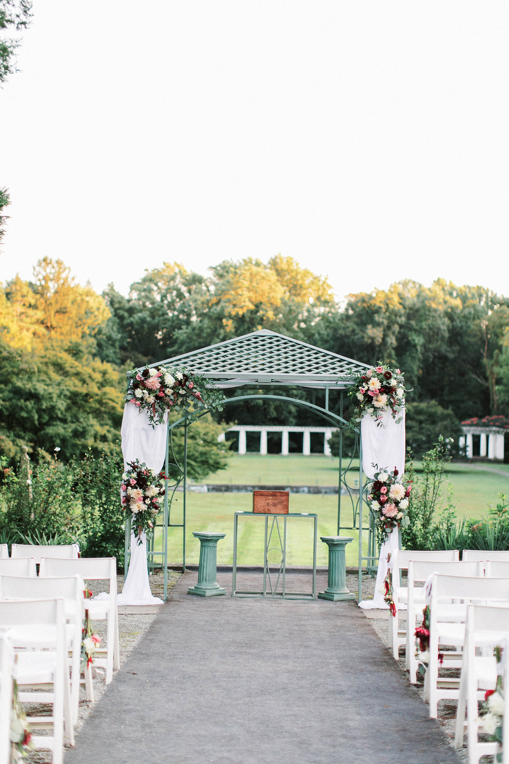We love how the bunches of flowers tied to the end of the rows add color to the aisle and lead your attention to the focal point at the arbor.