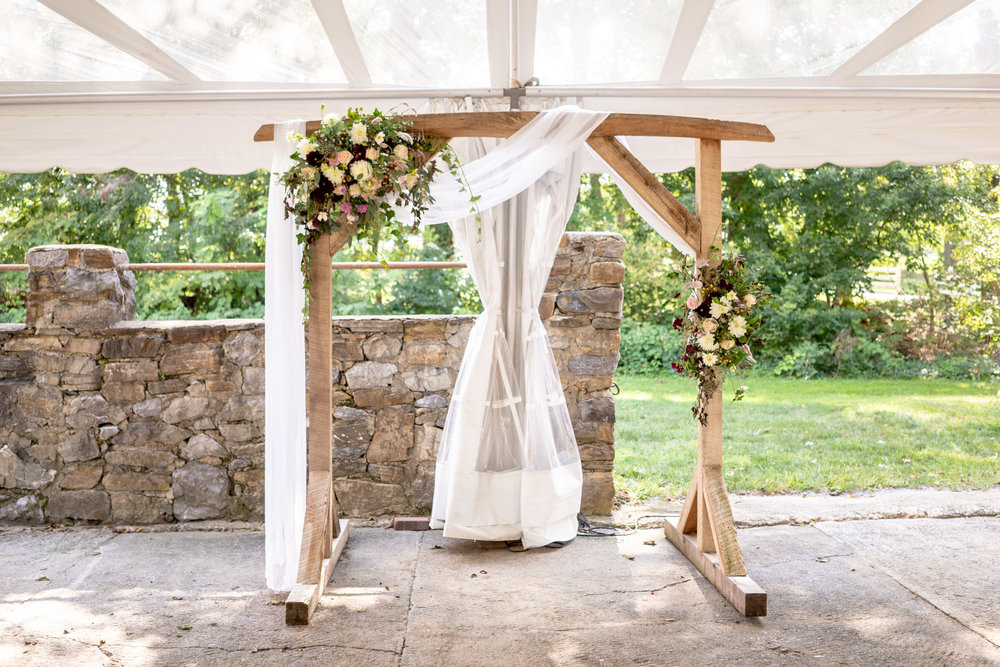 The ceremony was framed by this asymmetrical arbor with two of our custom floral sprays and a simple white draped tulle. The perfect backdrop for the most important part of the day!