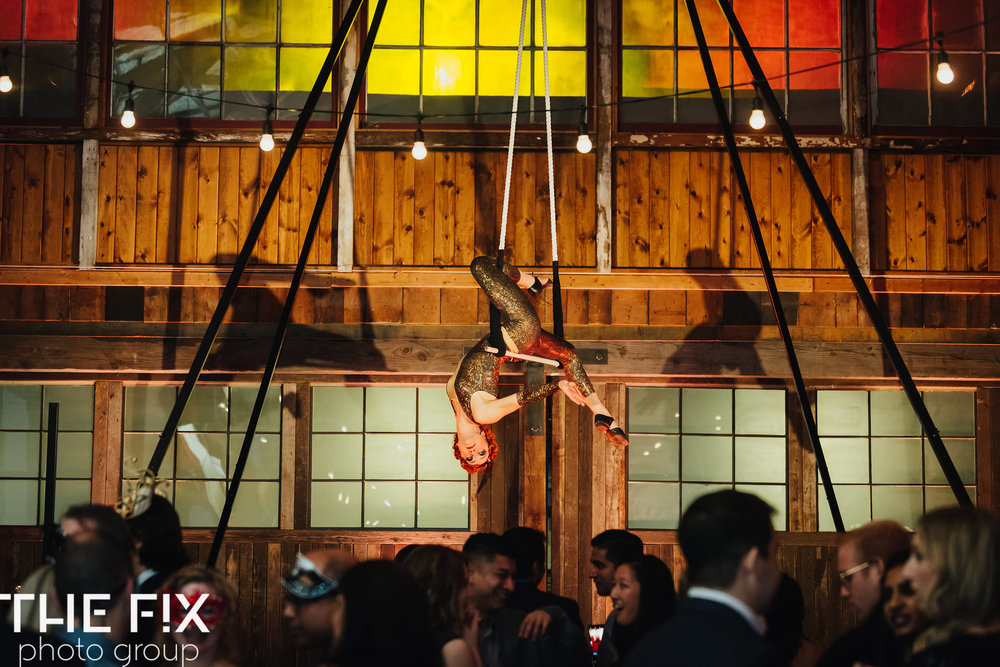 aerialists  hang over guests at a Corporate holiday party entertainment at Herban Feast , photographed by the Fix Photo Group