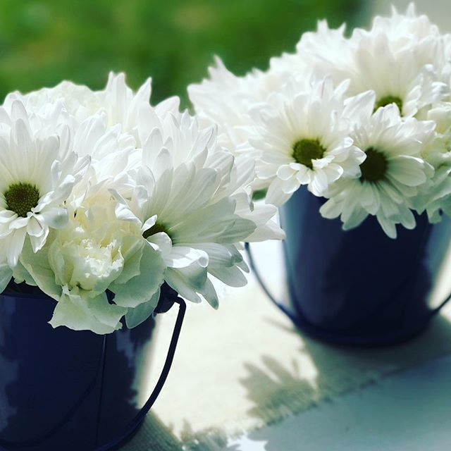 #MemorialDayWeekend is here! Hosting a BBQ? We have an easy centerpiece idea that's simple and affordable. Head to your local grocery story for white carnations and daisies, trim the ends, arrange in a jam jar, and place that jam jar into a little metal bucket, like these blue ones featured here from @target - and voila!  Pro tip: the jam jar stops the buckets from leaking all over the rest of your #MDW spread.  Cheers to the weekend! #centerpieces #tablescapes #blooms #whiteandblue #eventdesign #laceandblooms