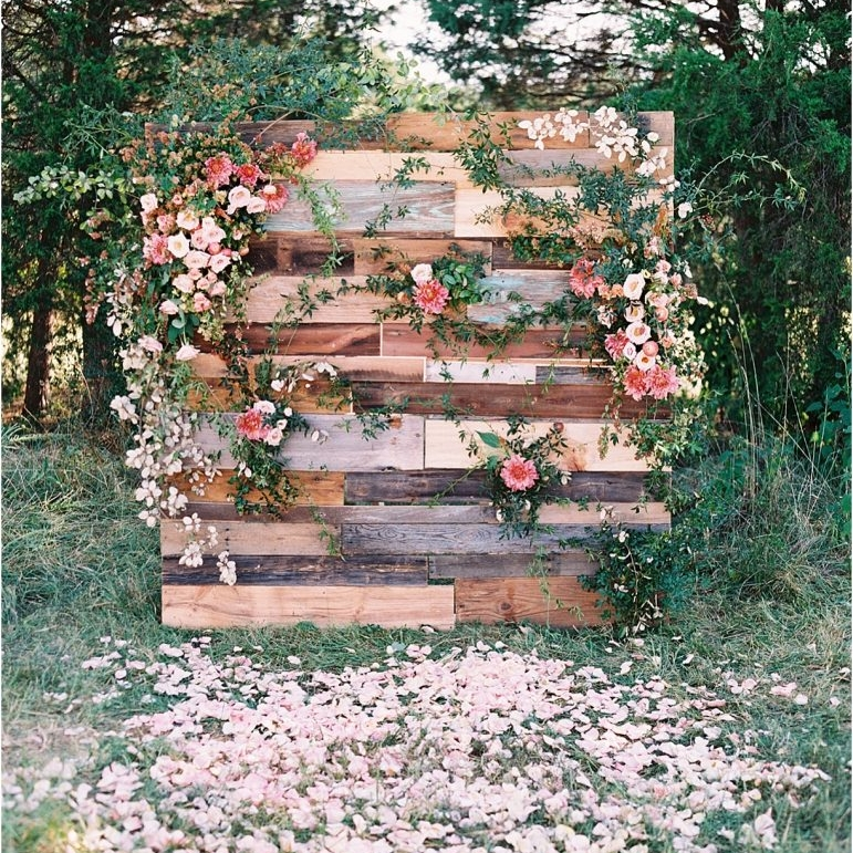 1. Rustic Backdrop - A floral drenched ceremony backdrop? Yes please! We can't think of a better rustic wedding DIY than this repurposed wood pallet ceremony backdrop. It is the perfect addition to any outdoor or country inspired wedding!