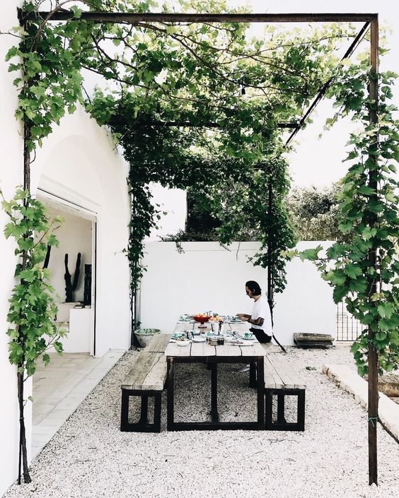Pebble/stones? might be too messy, likely ending up all over the yard? … but I like the white/black/green colour palette, the greenery 'shade' and the outdoor setting.