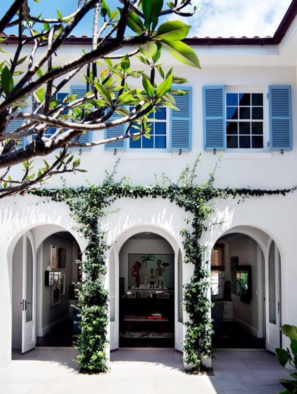 Greenery up the walls, curves in the architecture, a white exterior.