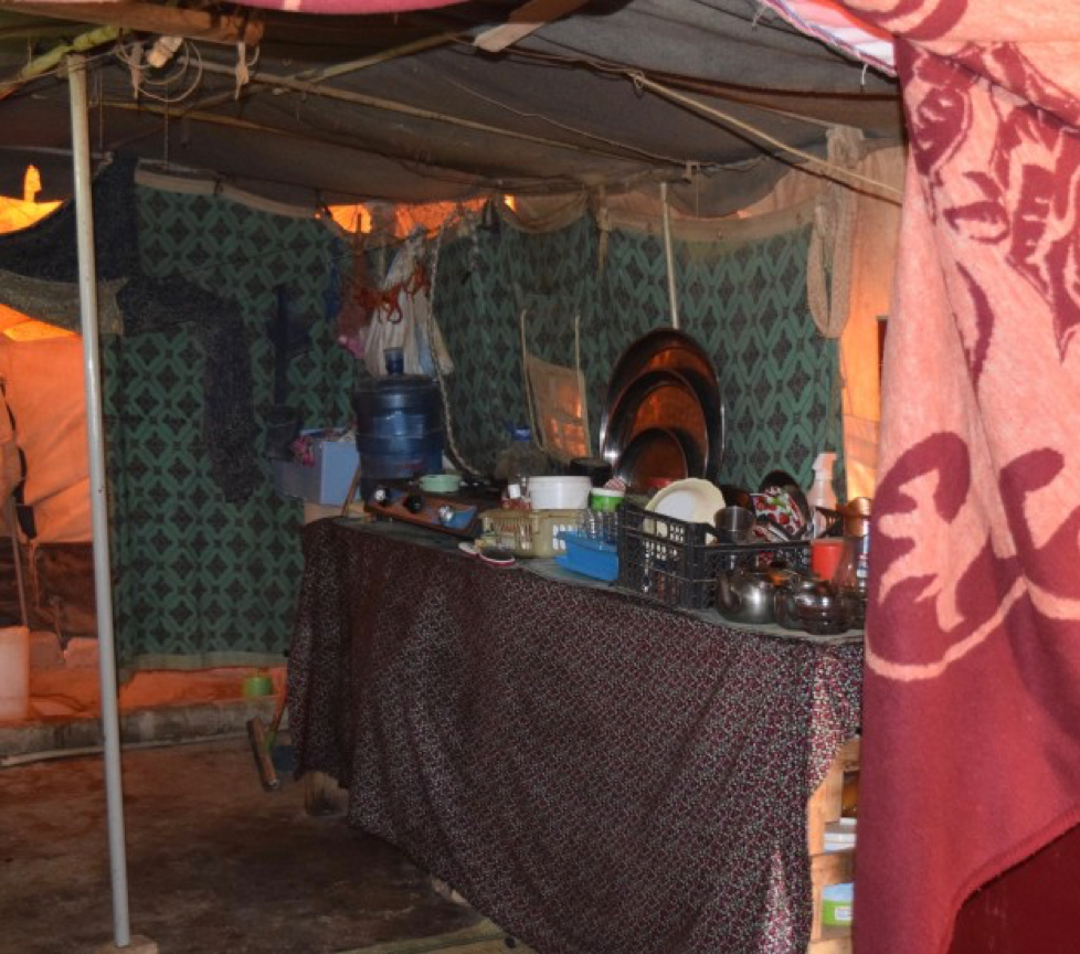 Most of the tents are set up in order to function on basic electricity, but unfortunately there is no running water. Here you can see the kitchen setup on the right, with a water jug in the corner. In the back, you can just see the area that is used for a bathroom, with the bucket on the floor. The 'rooms' are divided off by hanging large sheets of fabric in order to try to provide some privacy.