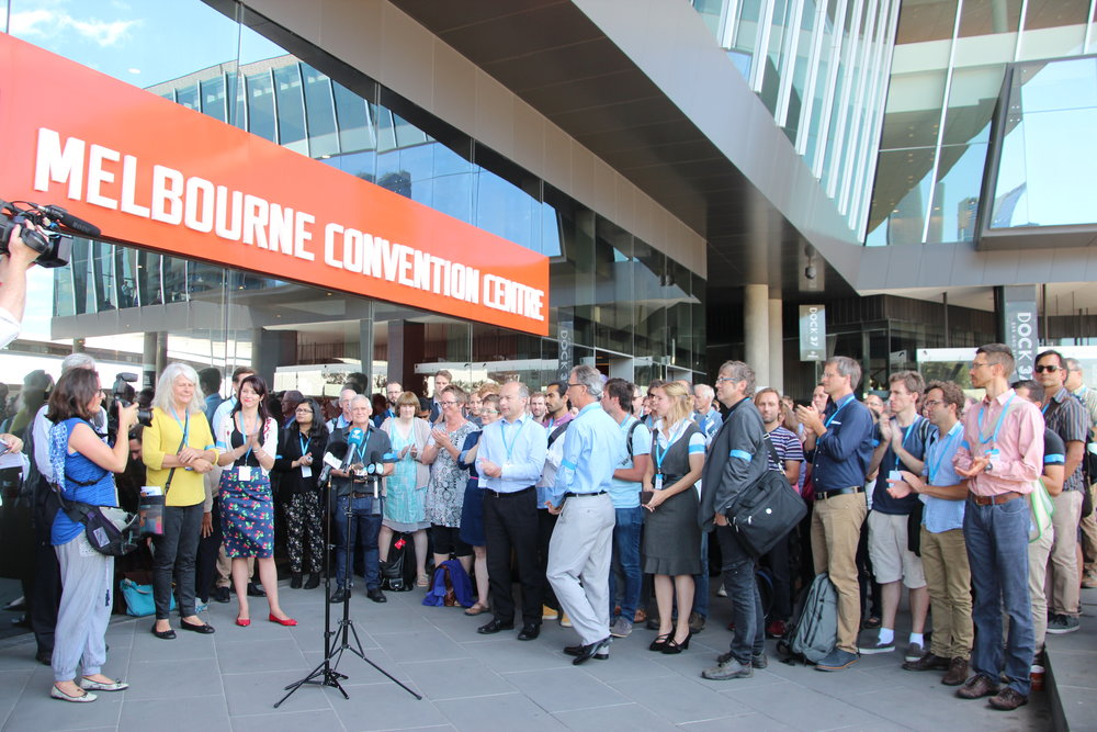 Over 100 climate scientists attending the Australian Meteorological and Oceanographic Society (AMOS) climate science conference in Melbourne, including international visitors, staged a lunchtime protest expressing disapproval of the restructure and cuts to CSIRO staff and climate research programs. Image by John Englart, Australia, 2016.