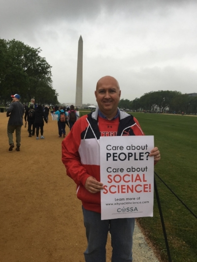 """Craig Scott stands on the National Mall during the March for Science, holding a sign that reads """"Care about PEOPLE? Care about SOCIAL SCIENCE! Learn more at www.whysocialscience.com"""". Photo courtesy of Craig Scott"""