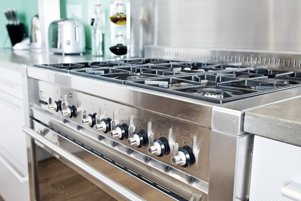 stock-photo-close-up-shot-across-cooker-in-modern-colourful-kitchen-56404789.jpg