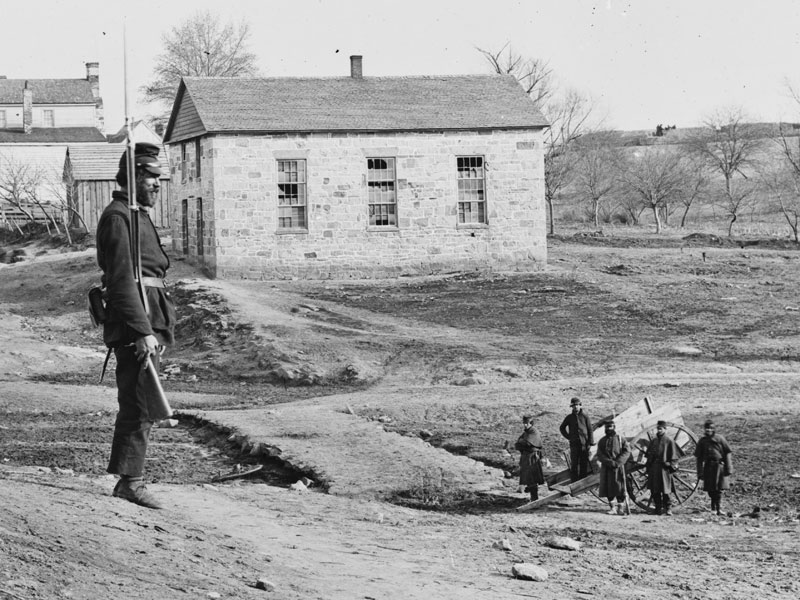 March, 1862.  This sentry is wearing dark blue trousers shortened by cutting off the cuffs, and the other five men also appear to be wearing dark blues. (LOC#: LC-B811-302)