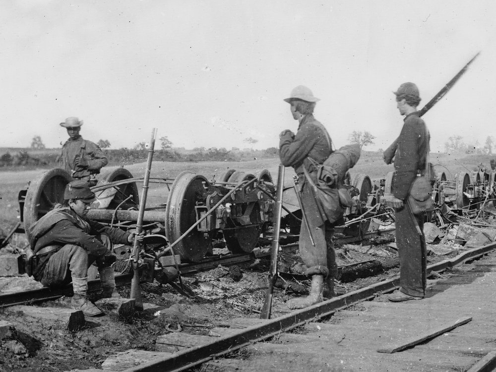 August, 1862. Soldiers beside damaged rolling stock of the Orange & Alexandria Railroad, near Manassas Junction, Va. One of my personal favorite photos, it shows a mix of the man on the right wearing dark blues, with the other two wearing sky blues. (LOC#: LC-B815-593)