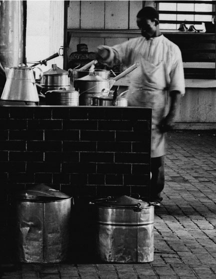 This cook has his hands full with numerous pots and kettles on an impressive stove. Notice the variety of lids and handles. Also note the bails ears and handles of the large kettle on the floor. These vary from the simplified style seen in most camps.