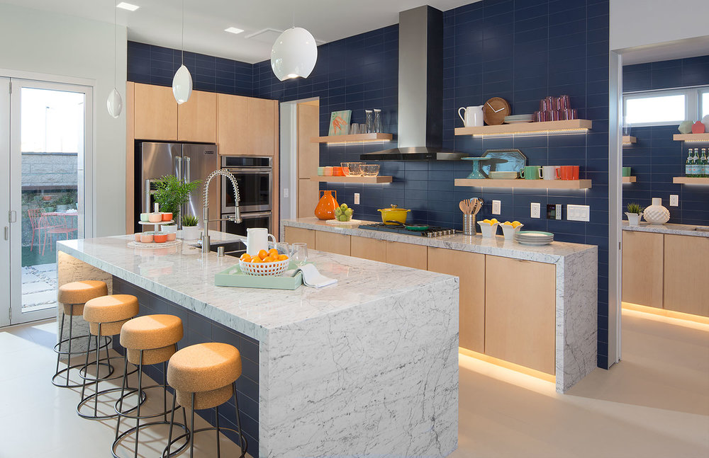 "Cabinets by Timberlake - The ""Lausanne Maple"" with Natural Finish (shown) is an upgrade cabinet option. Waterfall Edge countertop (shown) is an upgrade cost. Slate Blue Matte tile backsplash (shown) is an upgrade cost."