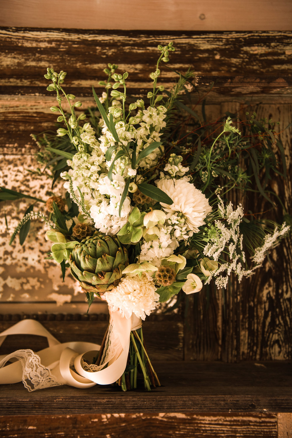 A Green and White Boho Wedding. A unique green and white loose wildflower bouquet with artichoke focal. | Flowers by Flower Buds | Photograph by Heart and Oak Photography | Venue The Ruins at Kellum Valley Farm