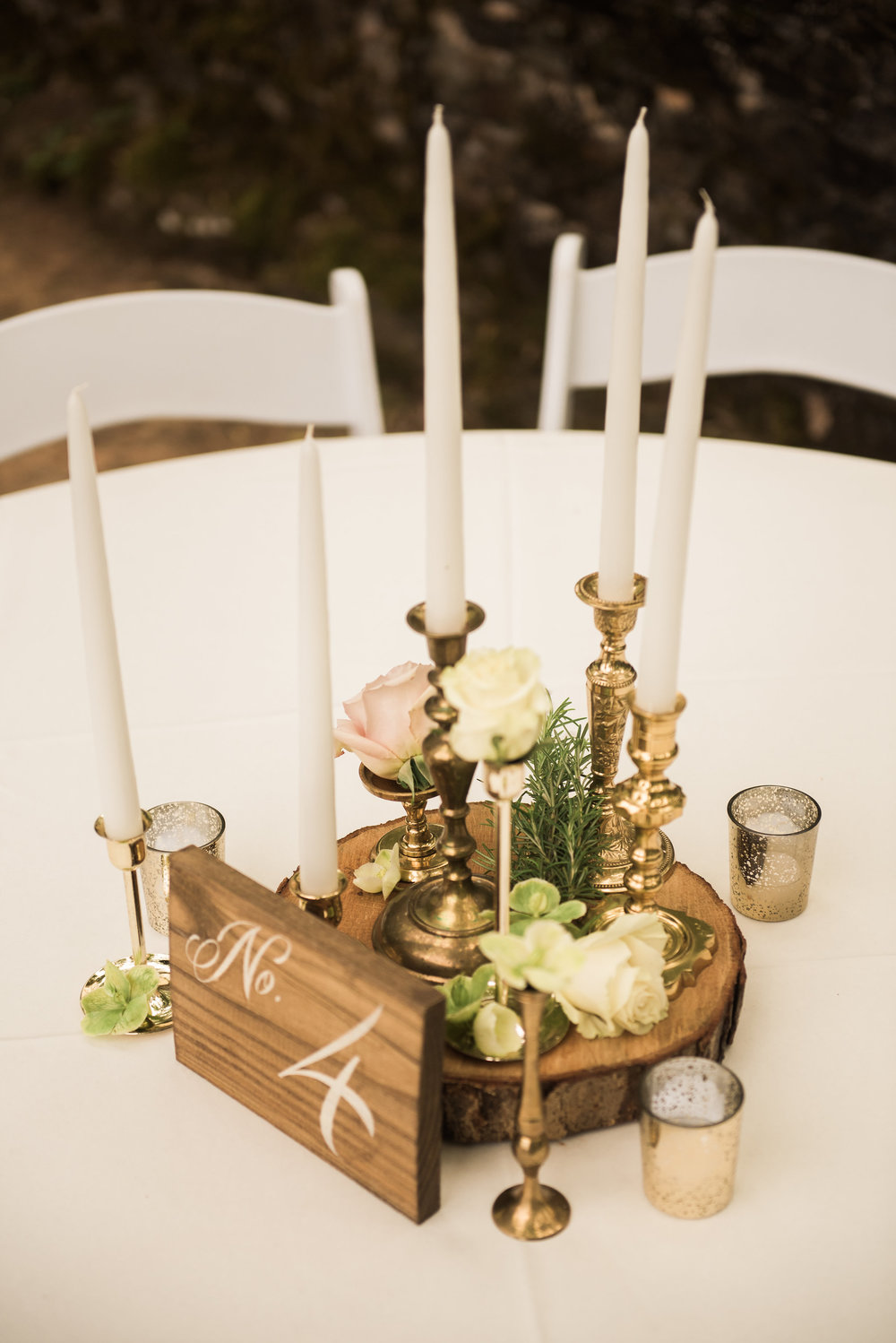 A Green and White Romantic Boho Wedding. An elegant but rustic boho table centerpiece with antique brash candlesticks, wood slabs and floral accents. | Flowers by Flower Buds | Photograph by Heart and Oak Photography | Venue The Ruins at Kellum Valley Farm