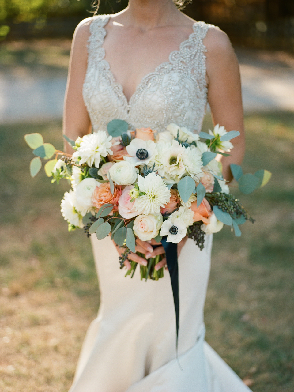Peaches and Cream Bridal Bouquet featuring white anemones, peach roses, white ranunculus, white dahlias, privet berry and silver dollar eucalyptus. | Flowers by Flower Buds. Photo by Davy Whitener Photography. Venue The Ruins at Kellum Valley Farm