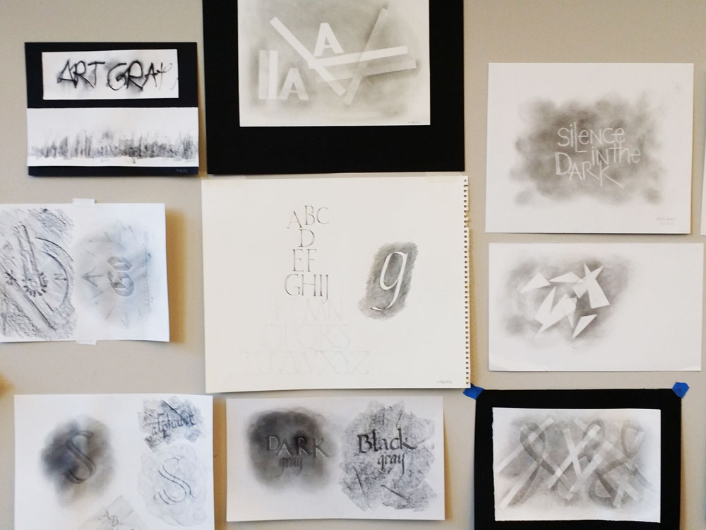 Students' experimentations with graphite were taped to the wall to admire and learn from.