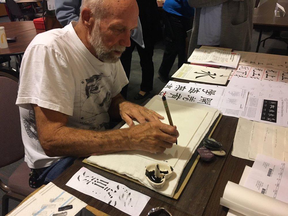 Gary Feyen demonstrates Chinese calligraphy at October's Demo Corner.