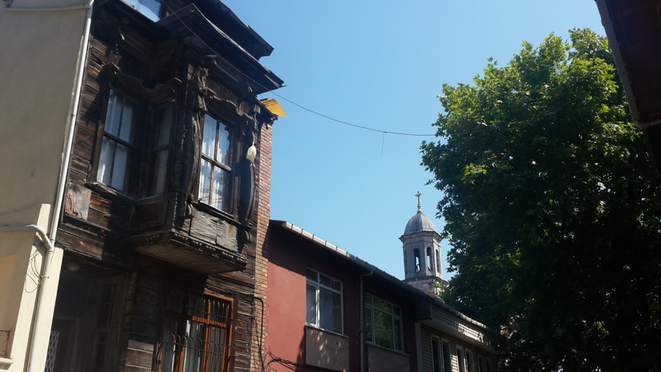 An old wooden house on The Gardens of Silihtar street, with the bell tower of Sourp Garabed Armenian Apostolic church seen in the background.