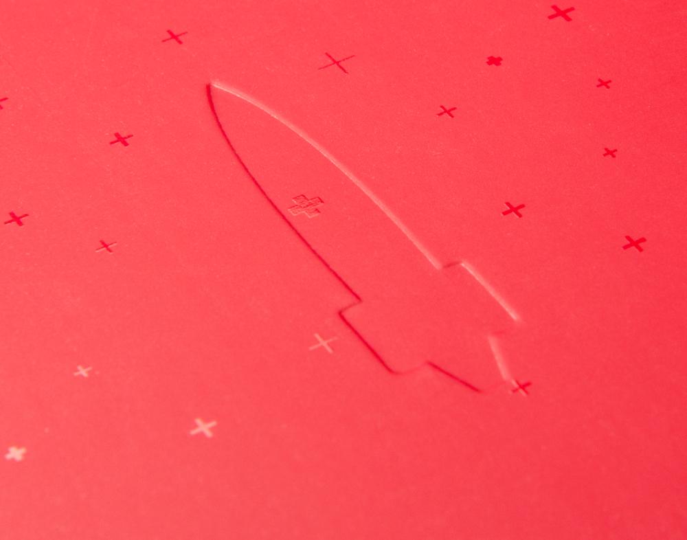 Detail von der Raketen Prägung und den Plus Symbolen von der Veranstaltungseinladung von Red Bull für die Einladungsreihe 123 Rakete. Gestaltet von den sons of ipanema.