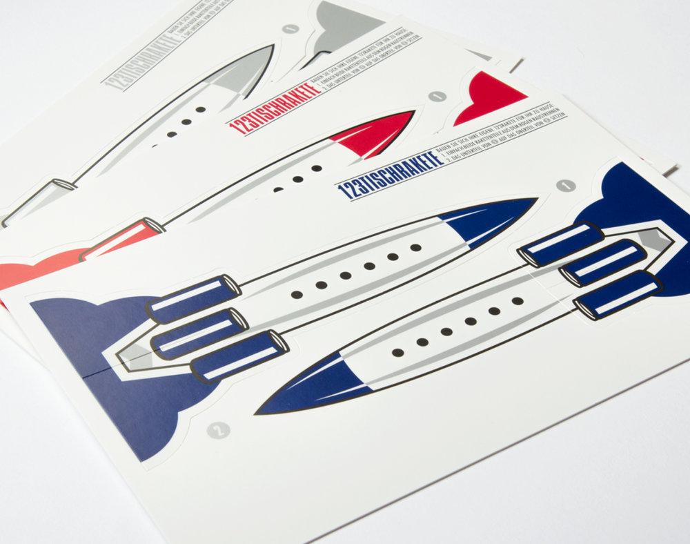 Blaue und rote Rakete auf weißem Hintergrund für die 123Tischrakte. Mit Perforierung um aus der Rakete eine kleinen Raktenaufsteller zu bauen. Für die Veranstaltungsreihe von 123 Rakte für Red Bull von den sons of panema in Köln gestaltet.