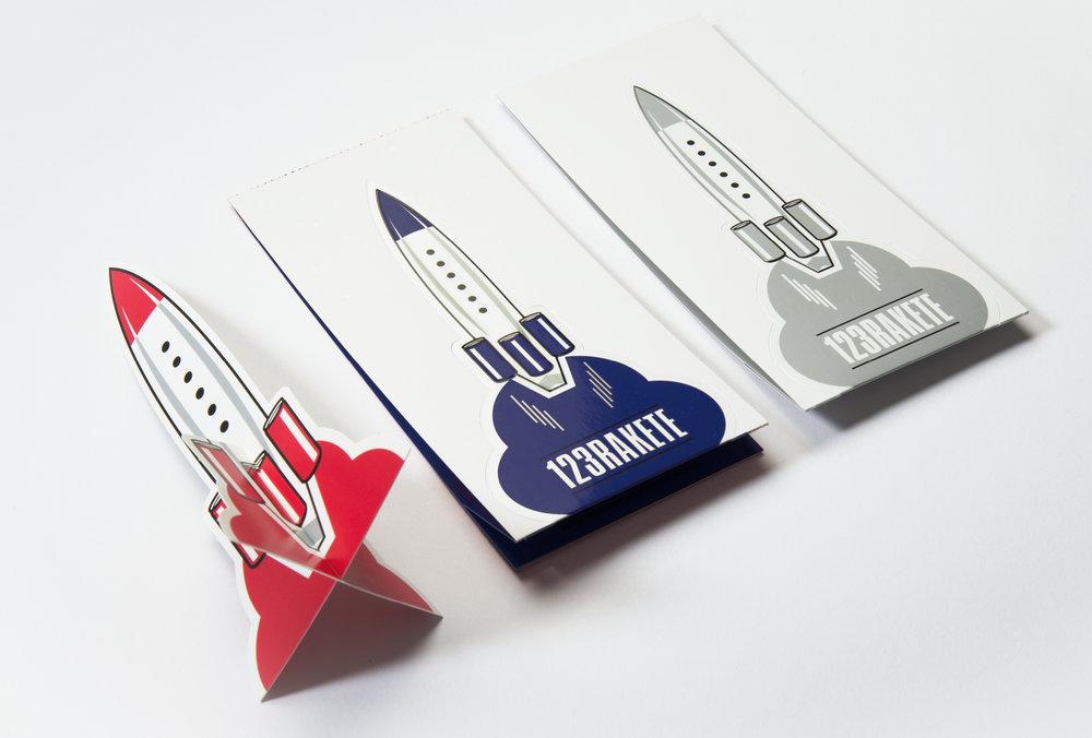 Illustration für eine graue, rote und blaue Rakete auf weißem Hintergrund für die 123Tischrakte. Mit Perforierung um aus der Rakete eine kleinen Raktenaufsteller zu bauen. Für die Party 123 Rakte von Red Bull gestaltet von den sons of panema, Grafikbüro in Köln.