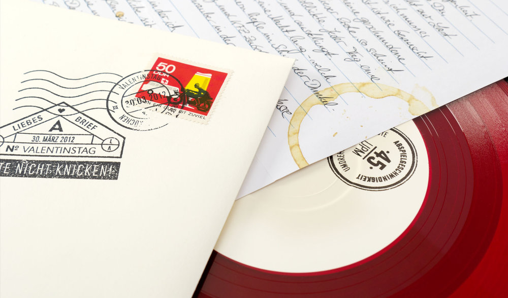 """Kreatives Cover Design für die Single """"Valentinstag"""" der Trierer Band Love A. Die sons of ipanema aus Köln haben Briefumschläge gestempelt und beschriftet. Rotes Vinyl und handgeschriebener Liebesbrief inklusive."""