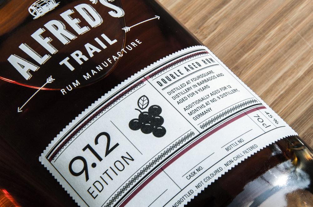 Etikett auf Flasche von dem Double Aged Rum, Edition 9.12 für Alfred´s Trail Rum Manufacture / Number Nine Spirituosenmanufaktur von den sons of ipanema einem Studio für Grafik aus Köln. Mit Trauben und Fass Icon sowie Logogestaltung und Verzierung.