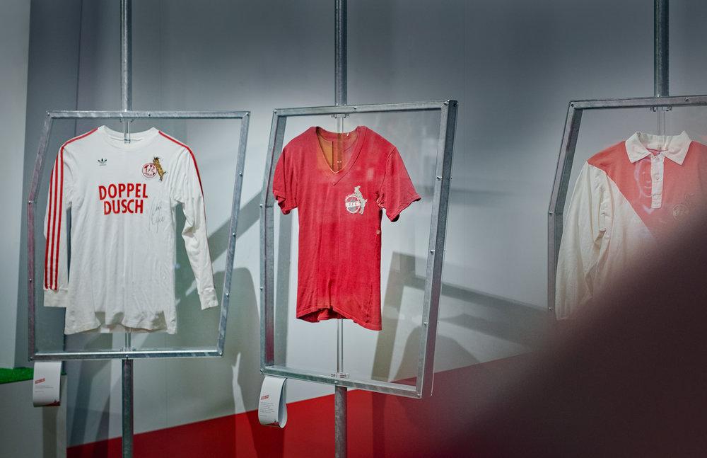 """Trikotgalerie in der Ausstellung """"70 Jahre FC – Die Zeiten ändern sich, das Gefühl bleibt."""" des 1. FC Köln, die von den sons of ipanema (Design Studio/Köln) in Zusammenarbeit mit buntebrause und designbauwerk gestaltet wurde."""