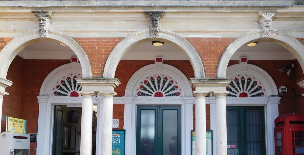 Faces above the three entrance arches of North Dulwich station