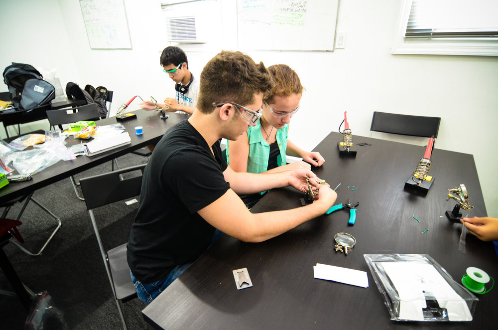 Engineering instructor teaching student engineering through soldering their own sound to light sensors