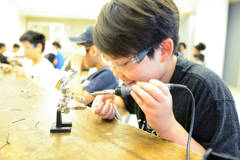 Students working and soldering circuitry