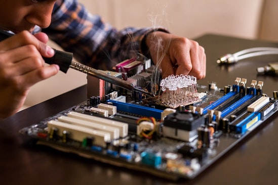 Student soldering circuitboard during stem summer program