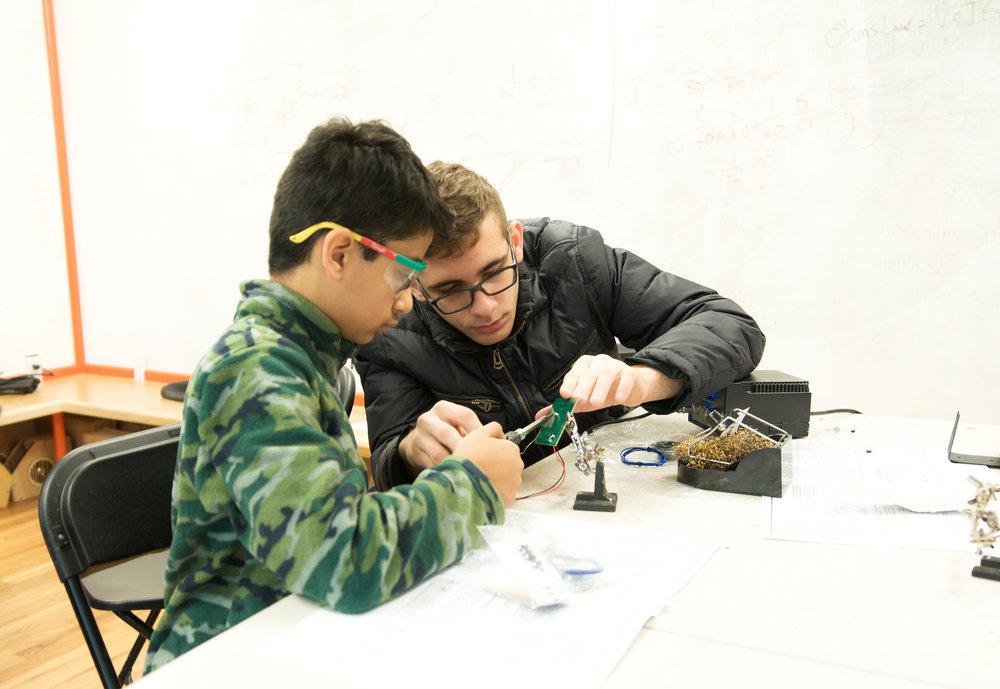 Mentor Helping Student Solder Circuitboard during stem program