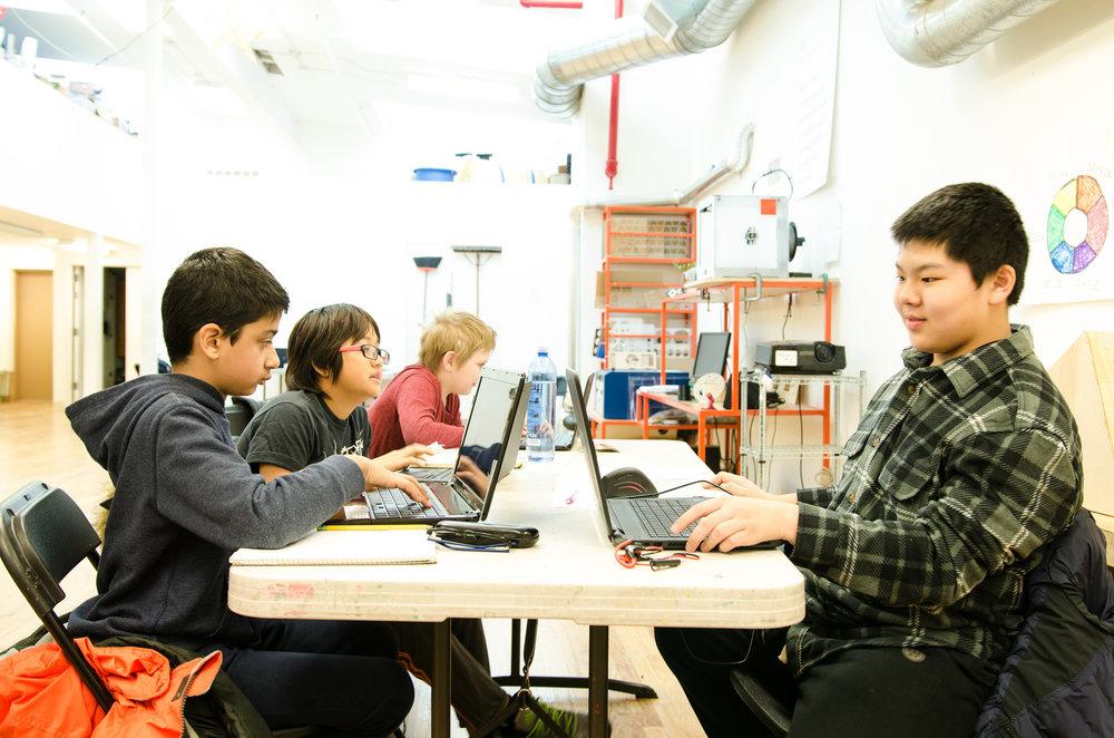 Students coding websites on laptops together during stem program