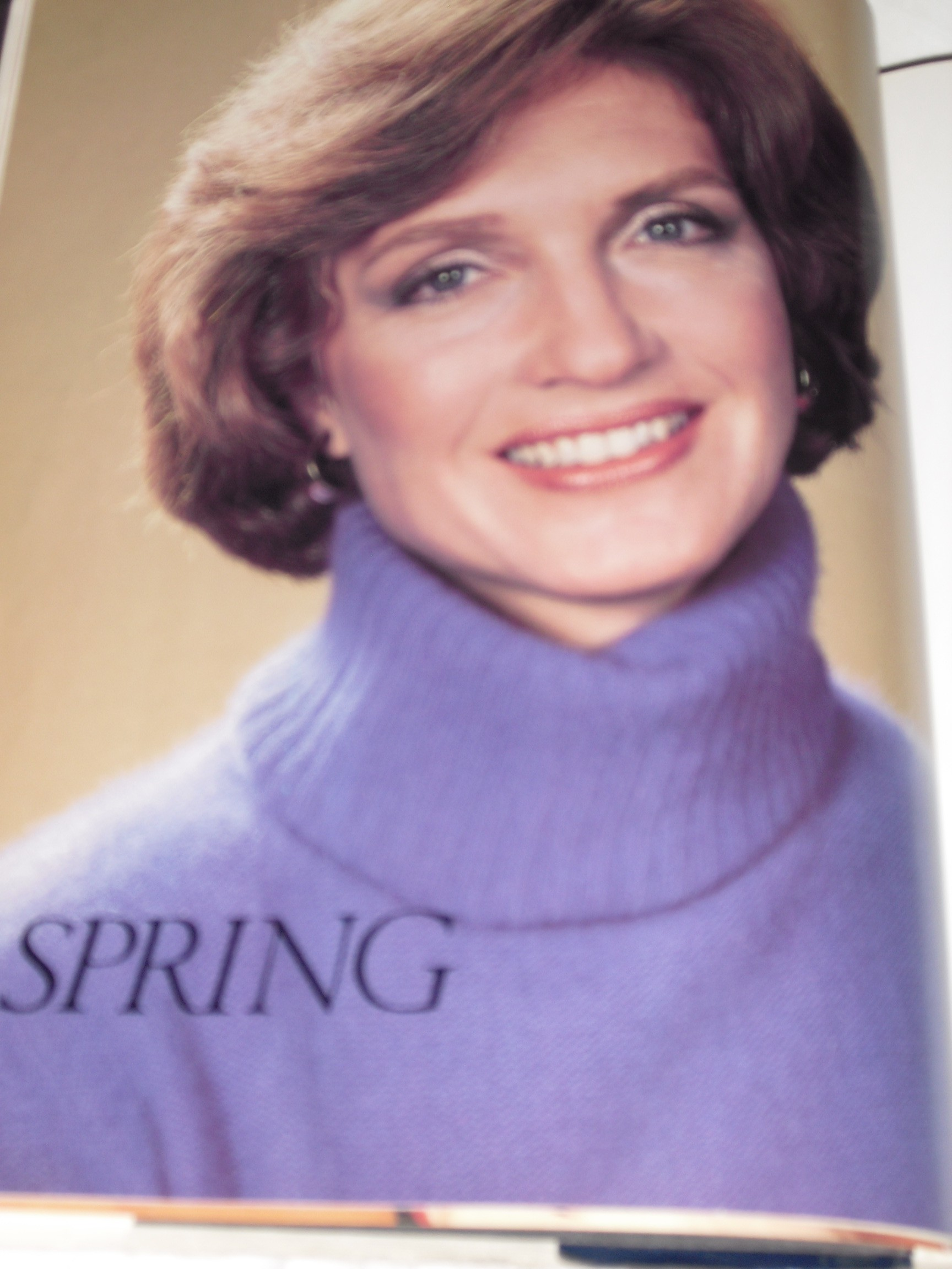Picture of woman in purple turtleneck with 80's hair / makeup
