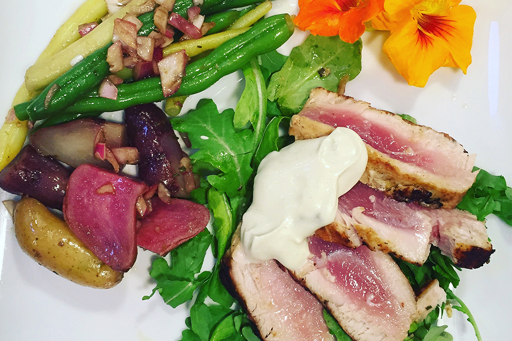 Ingredients:   4 - 6oz Ahi Steaks  1 tsp toasted sesame oil  1 Tbsp olive oil  1 tsp  Chef Josef's Curry Basil or Chef Josef's Original  blend    ¾ lb fingerling potatoes or red potatoes  ¾ lb green beans  1/2 cup chopped red onion  1 Tbsp sweet butter  ½ tsp  Chef Josef's Lemon Dill  blend     Sauce for Ahi:   ½ c Mayonnaise  1/2 cup sour cream  ½ tsp  Chef Josef's Curry Basil  or  Tarragon Citrus  blend  Mix all ingredients and place in refrigerator.    Steam beans and potatoes.  Heat butter in skillet and sauté onion until translucent.  Add beans and potatoes to the skillet and sauté until hot.  Keep warm.    Season the Ahi steaks with the seasoning blend.  Heat oil on high in a cast iron skillet.  Sear Ahi quickly on both sides in the hot oil.  If you like your Ahi rare it should not take more than a few minutes on both sides.