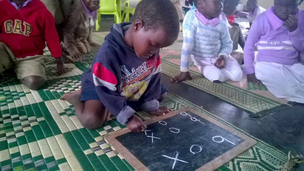 Namakula, learning to read at write at the nursery school in Loco slum, Uganda