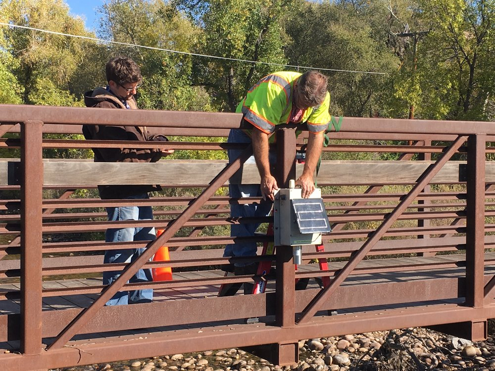 Sean McFeely (left) Product Manager for RiverTrak, assists Dan Ceynar (right) of Iowa Flood Center to install a Sensor on the Poudre River near Bellvue.