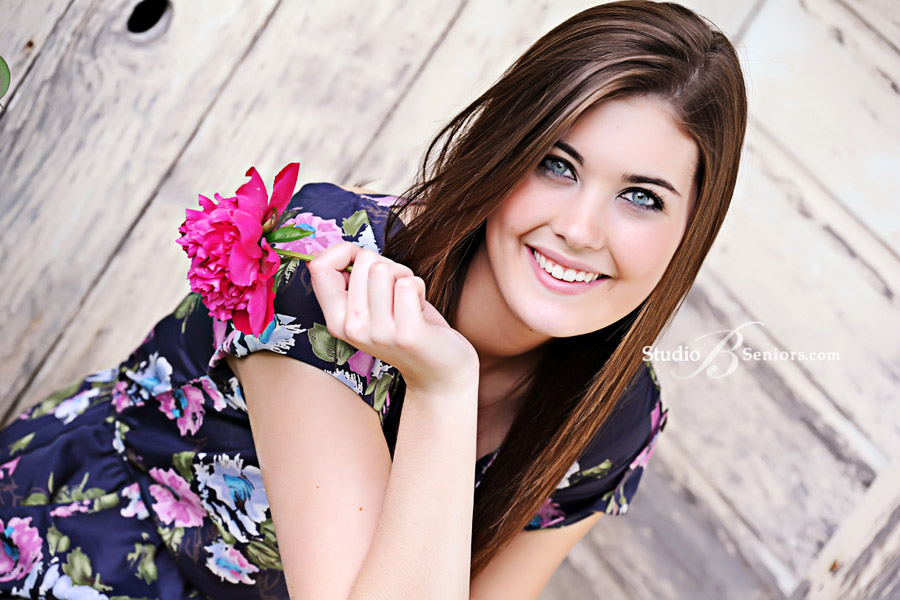 Mercer-Island-High-School-Senior-Pictures-of-pretty-girl-with-flowers-near-rustic-white-barn