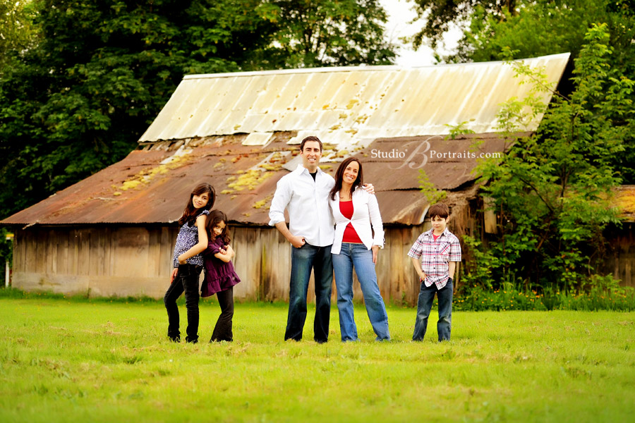 Modern-family-pictures-of-attractive-family-in-field-with-rustic-barn-in-Issaquah-near-Seattle